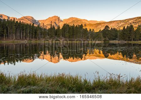 Hallett Peak reflection in Sprague Lake at sunrise, in Rocky Mountain National Park, near Estes Park, Colorado.