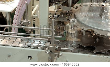 Bottling conveyor product line for pouring beverages into plastic bottles. Robotics and automatic lines instead of human labor on factories and plants.