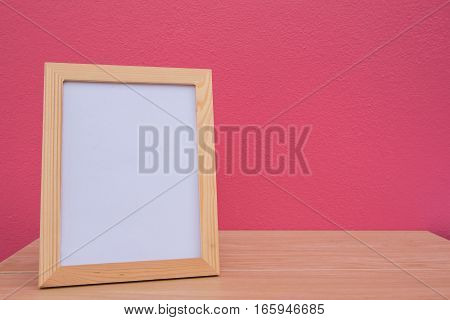 photo Frame on a wooden on pink background .