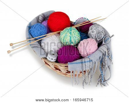 Balls of yarn in a basket with knitting needles, scissors and measuring tape