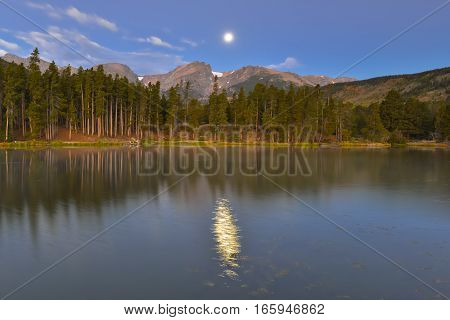 Harvest moon over Hallett Peak reflecting in Sprague Lake, in Rocky Mountain National Park, near Estes Park, Colorado.