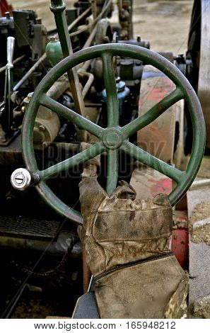 A gloved hand operates the steering wheel of a very old steam driven tractor