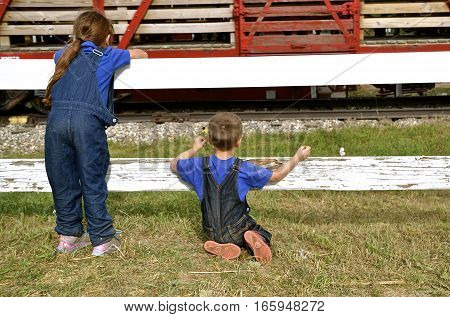 ROLLAG, MINNESOTA, Sept 1. 2016:Two unidentified children peer through a fence as they watch a passing freight train at the West Central Steam Threshers Reunion in Rollag, MN attended by 1000`s held annually on Labor Day weekend.