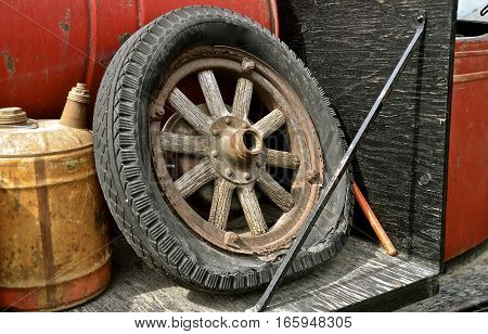 A rotten flat tire with a rusty rim and wooden spokes is stored  next to several old cans and barrels