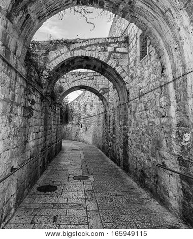 Ancient narrow street in old city of Jerusalem, Israel. B&W filtered image for retro style