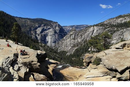 YOSEMITE NATIONAL PARK - SEP 22: Hikers take in the view of Yosemite Valley from the top of Nevada Falls on Sep 22, 2015 in Yosemite National Park. Nevada Falls is located at the west end of Little Yosemite Valley.
