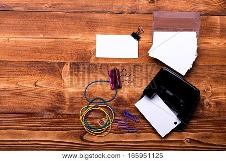 set of stationery for office: paper clips binder clips box with blanks rubber band hole puncher on brown vintage wooden background top view copy space