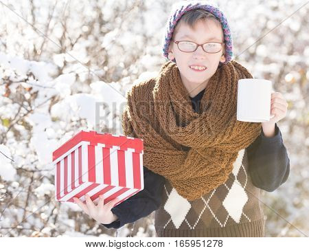 Small Boy With Present And Cup In Winter Outdoor