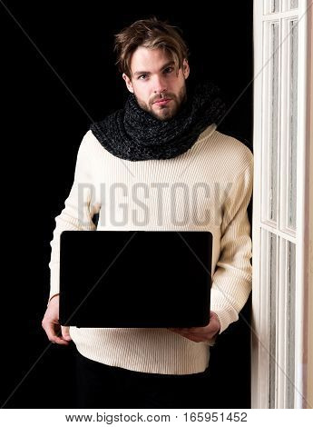 handsome bearded man or guy with beard on face in white sweater and knitted on black background near wooden door holds laptop copy space