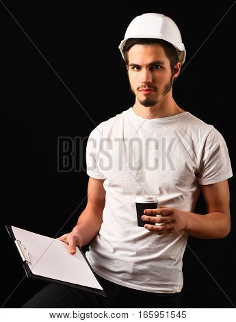 handsome bearded builder or foreman in white shirt and helmet on serious face holding tablet with coffee cup on black studio background copy space