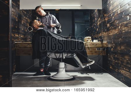 Young Bearded Man Getting Beard Haircut By Barber While Sitting In Chair At Barbershop. Barbershop Theme
