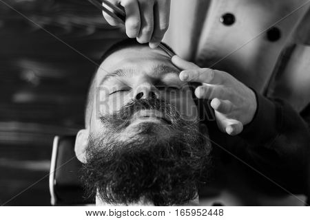 Young Bearded Man Getting Haircut With A Straight Razor By Barber. Barbershop Theme