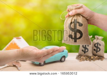 Loans for real estate concept. Hand with bag dollar sign giving money to another hand on green and yallow bokeh background