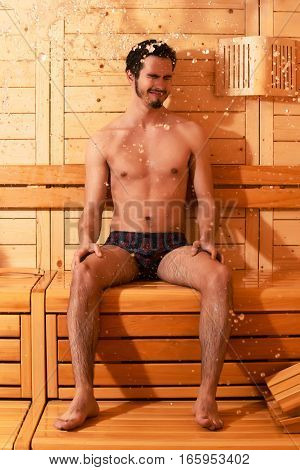 Handsome man or bather with muscular sexy torso body wet with big splash of water in sauna thermal bath on wooden background