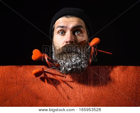 handsome bearded man or guy in winter hat with fashionable mustache on surprised face and snow in beard with decorative valentines hearts on sticks near red paper on black background copy space