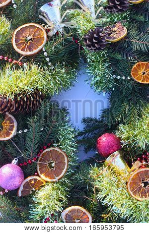 Frame of Christmas decor with dry orange slices and colorful balls on white snow background.