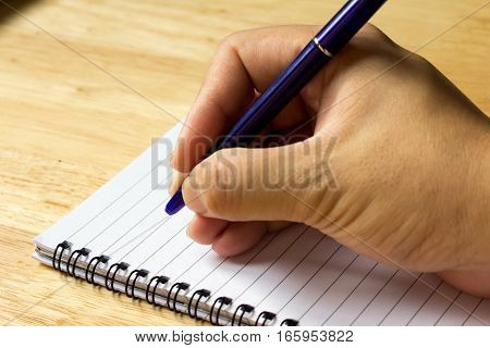 Business man write with pen on note paper ackground