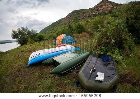 Boats and a tent on the banks of the river. Tourists were floated down the river and camped on a rainy day.