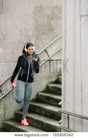 Sporty Woman Texting On Smartphone And Stretching