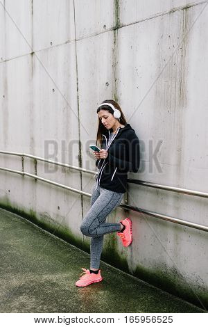 Sporty Woman With Headhphones Texting On Smartphone