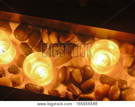 arrangement of glowing candles with rocks and sand in the dark. Calm, peaceful, quiet concept.