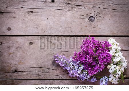 Spring background. Fresh aromatic lilac flowers on vintage wooden planks. Selective focus. Place for text. Floral still life.