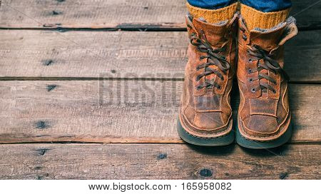 Feet wearing winter fur boots and wool socks on the wooden floor. Color toning