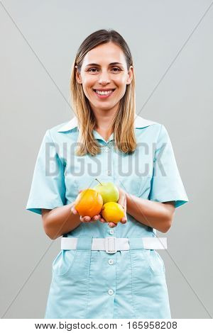 Beautiful nurse is holding fruit on gray backround.