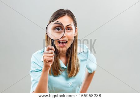 Photo of excited nurse looking through loupe.