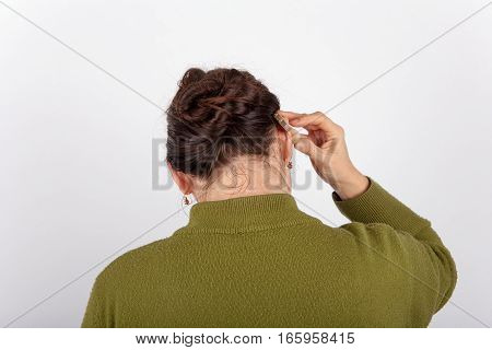 The woman is inserting her hearing aid