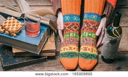 Feet and hands of person wearing colorful winter socks reading book and drinking wine