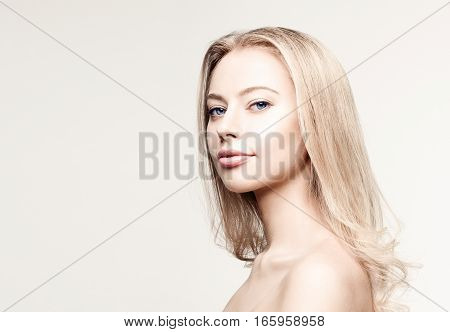 Young woman portrait. Closeup beauty studio shoot. Healthy clean skin and perfect makeup on beautiful face of white model with long blonde hair. Beautiful girl. Posing fashion model.