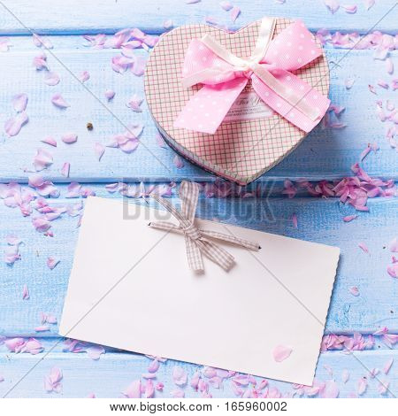 Box with present in form of heart petals of sakura pink flowers and empty tag on blue wooden planks. Selective focus is on tag. Place for text. Flat lay. Square image.