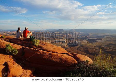 Two hikers enjoy the view form the Green River Overview, looking down into the valley carved by the Colorado and Green River. Canyonlands National Park, Utah, USA