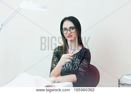 The girl beautician sitting in bright office glasses tools in the hands of