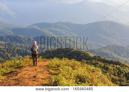 Tourist woman looks the beautiful scenery while trekking on Kew Mae Pan nature trail Chiang Mai Thailand