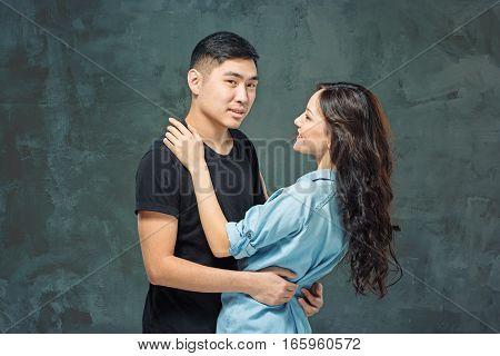 Portrait of smiling Korean couple on a gray studio background