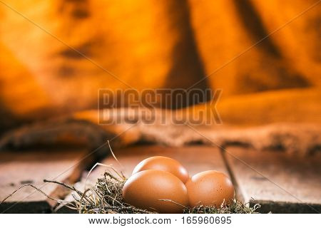 Uncooked chicken eggs in natural birds nest in front of wood boards and fire lighted burlap background