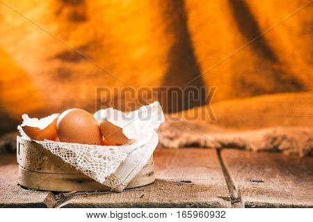 Uncooked chicken eggs in a sieve on wood boards over fire lighted burlap background