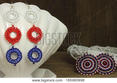 Earrings on white ceramic shell on wooden background