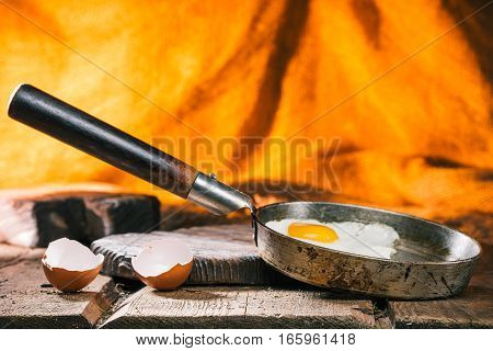 Cooked egg and broken egg shell on rustic table over firelight background