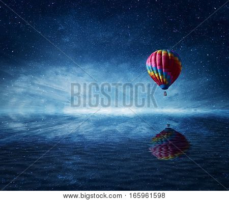 Hot air balloon flying over the a cold dark blue sea. Wonderful landscape with a starry night sky background and water reflection.