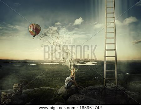 Young boy sit on the top of a hill near a ladder goind up in the sky and a hot air balloon fly over the forest valley. Bad mood hard thinking no inspiration concept with his head fired and the smoke rising up.
