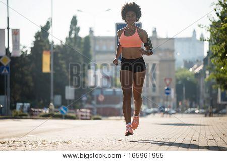 Fitness model running outside in summer. Listening to music.