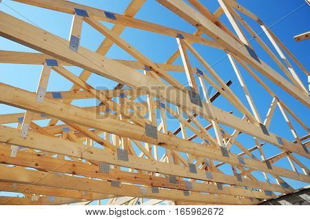 Timber Roof Trusses. New residential construction home framing against a blue sky. Roofing construction. Wooden construction