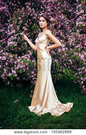 Portrait of young beautiful woman posing among spring blooming trees. Professional make-up and hairstyle. Perfect skin. Long evening dress. Fashion photo. Natural beauty.