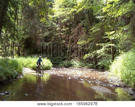 Picture of a cyclist riding through a shallow creek