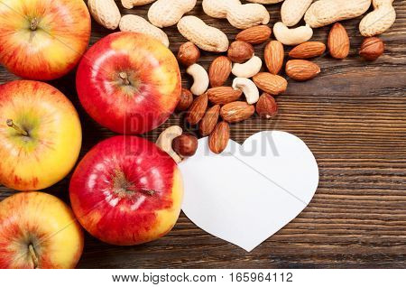 Ripe red apples and different nuts on a wooden background. Top view. Vegan concept.