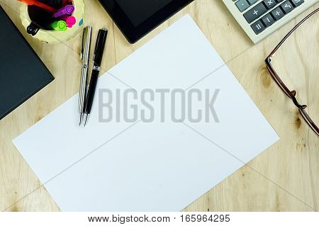 Blank paper and Office supply on table desk in top view. with light warm tone color effect.