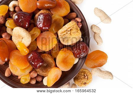 Dried fruits on a white background. Dates lemon apricots figs and nuts in a clay plate. Top view.
